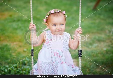 Adorable girl having fun on a swing on summer day stock photo, Adorable girl having fun on a swing on summer day. by timonko