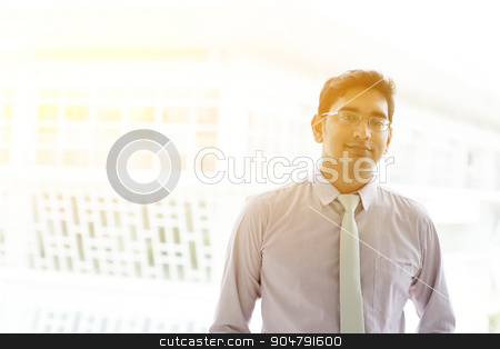 Asian Indian businessman stock photo, Portrait of 30s Asian Indian businessman standing outside office. India male business man, modern office building with golden sunlight at background. by szefei