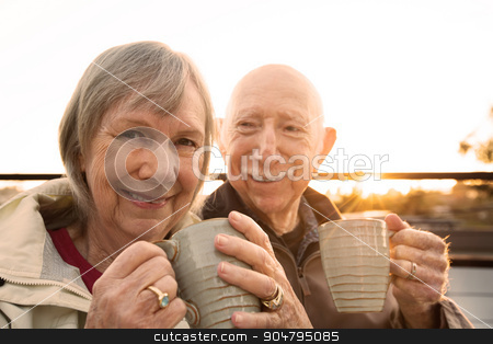 Cheerful Couple with Coffee Outdoors stock photo, Cheerful older couple sitting outdoors with coffee by Scott Griessel