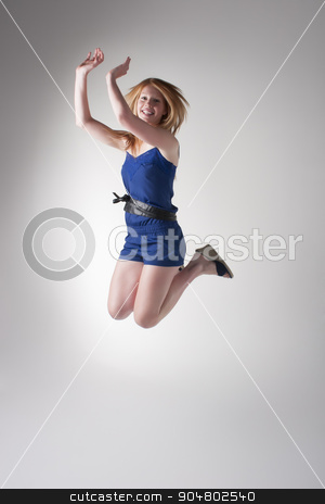 Happy redhead jumping stock photo, Cheerful readhead in a blue jumpsuit and black platforms jumping in a studio by JRstock