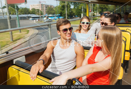 group of smiling friends traveling by tour bus stock photo, travel, tourism, summer vacation, sightseeing and people concept - group of smiling teenage friends in sunglasses with map traveling by tour bus by Syda Productions