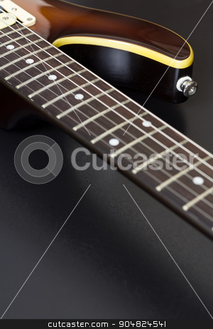 Electric Guitar Closeup stock photo, Closeup of a sunburst electric guitar with shallow depth of field on black and with copy space by Brigida Soriano