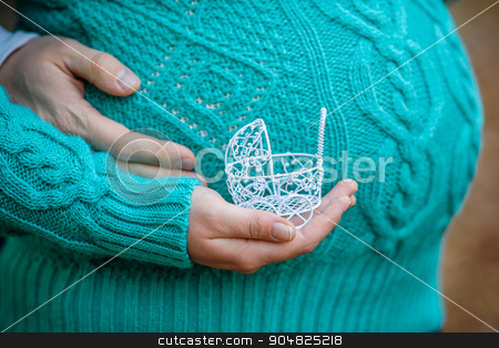 Pregnancy concept: belly with hand holding small toy stroller in front stock photo, Pregnancy concept: belly with hand holding small toy stroller in front. by timonko