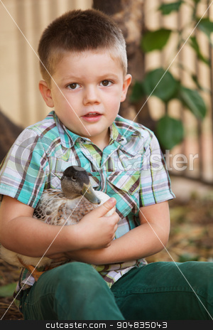 Cute Child Holding Duck stock photo, Single smiling child holding a duck outdoors by Scott Griessel