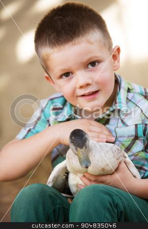 Little Boy Petting Duck stock photo, Smiling little boy petty a duck outdoors by Scott Griessel
