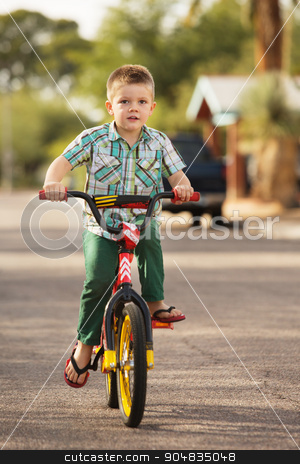 Boy Riding Bicycle stock photo, Single boy riding bicycle on street by Scott Griessel