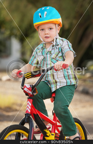 Child in Bike Helmet Riding stock photo, Single child in helmet riding a bicycle by Scott Griessel