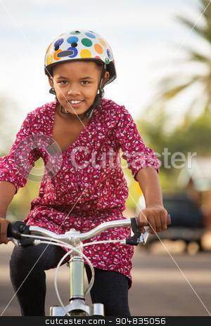 Happy Girl Riding Bike stock photo, Happy African American girl in helmet riding bike by Scott Griessel