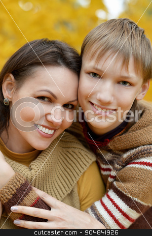 mother with a boy stock photo, Beautiful mother with a boy on a walk during the fall of the leaves in the park by Ruslan Huzau