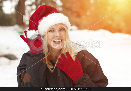 Attractive Santa Hat Wearing Blond Woman Having Fun in Snow stock photo, Attractive Santa Hat Wearing Blond Woman Having Fun in The Snow on a Winter Day. by Andy Dean