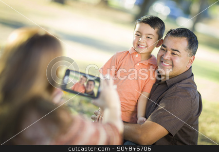Mixed Race Family Taking A Phone Camera Picture stock photo, Happy Mixed Race Family Taking A Phone Camera Picture At The Park. by Andy Dean