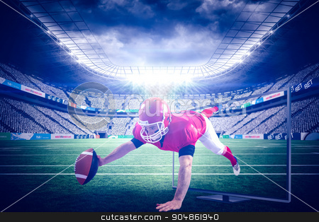 Composite image of american football player reaching football stock photo, American football player reaching football against rugby stadium by Wavebreak Media