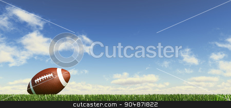 American football ball, on the grass, with fluffy couds sky in t stock photo, American football ball, on the grass, with fluffy couds sky in the background. Side view, from ground level, panoramic format. by Leonello Calvetti