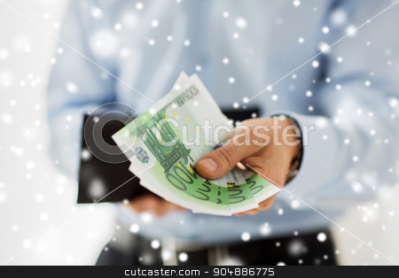 close up of businessman hands holding money stock photo, people, business, finances and money concept - close up of businessman hands holding open wallet with euro cash over snow effect by Syda Productions