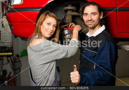 Auto mechanic and female trainee in garage stock photo, Women in male-dominated professions: Auto mechanic is happy with the success of a female trainee during maintenance of the brake disc of a car in a garage. Concept for the fact that more and more by Frank G?