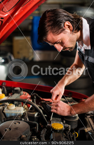 Auto mechanic fixing car engine stock photo, Portrait of an auto mechanic fixing the engine of a car with open hood by Frank G?