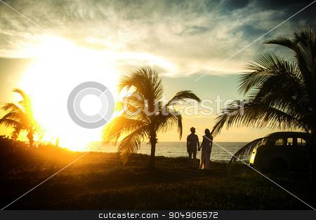 couple standing near palms on their honeymoon in sunset stock photo, couple standing  near palms on their honeymoon in sunset by Volodymyr Ivash
