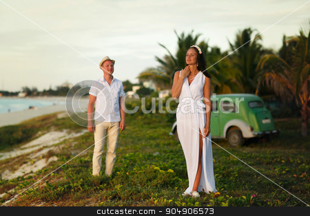 stylish couple standing on the beach and palms stock photo, stylish couple standing  on the beach and palms by Volodymyr Ivash