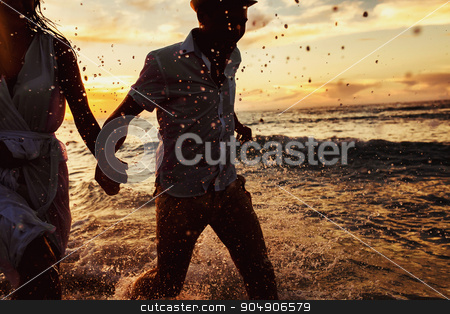 beautiful sunset in the ocean and happy couple running together stock photo, beautiful sunset  in the ocean and happy couple running together by Volodymyr Ivash