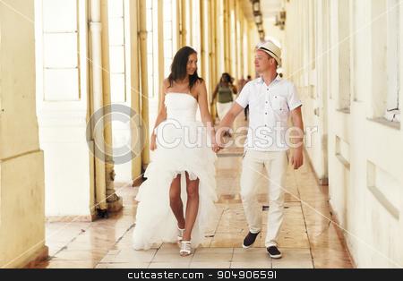 Happy stylish wedding couple holding hands in old city stock photo, Happy  stylish wedding couple holding hands in old city by Volodymyr Ivash