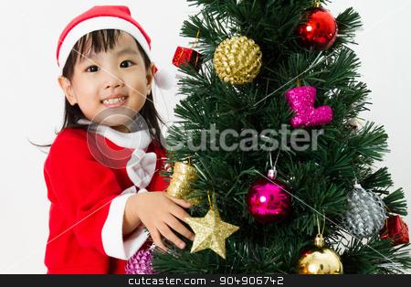 Asian Chinese little girl posing with Christmas Tree stock photo, Asian Chinese little girl posing with Christmas Tree on plain white background studio. by Tan Kian Khoon
