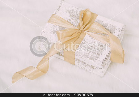 Shabby chic gift with golden ribbon on white  background stock photo, Beautiful Christmas gift on fluffy carpet by sunapple