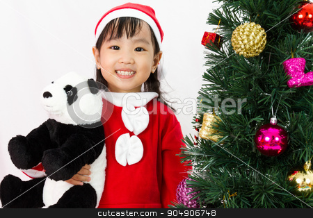 Asian Chinese little girl holding panda doll posing with Christm stock photo, Asian Chinese little girl holding panda doll posing with Christmas Tree on plain white background studio. by Tan Kian Khoon