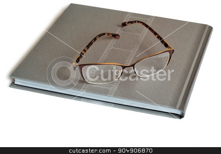 Glasses and notebook on a white background. stock photo, On notebook gray points lie in a beautiful frame. Presented on a white background. by Georgina198