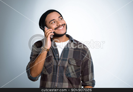 Freestyle photo with young mulatto stock photo, Young mixed race man with beard standing on grey background. Young man smiling and using mobile phone by Dmytro Sidelnikov