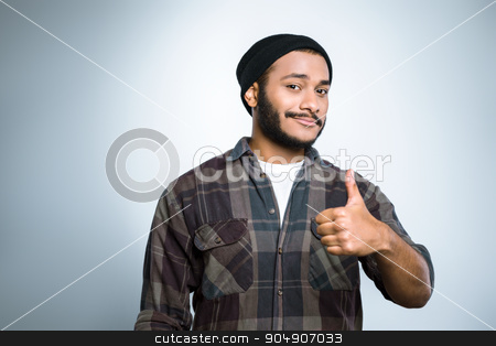 Freestyle photo with young mulatto stock photo, Young mixed race man with beard standing on grey background. Young man smiling and showing thumb up by Dmytro Sidelnikov