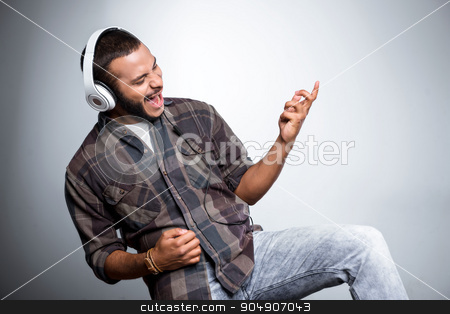 Freestyle photo with young mulatto stock photo, Young mixed race man with beard standing on grey background. Young man listening to music and pretending to play guitar by Dmytro Sidelnikov