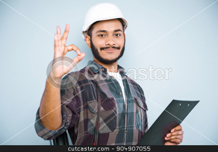 Freestyle photo with young mulatto stock photo, Young mixed race man with beard and helmet standing on grey background. Young builder smiling and showing ok sign by Dmytro Sidelnikov