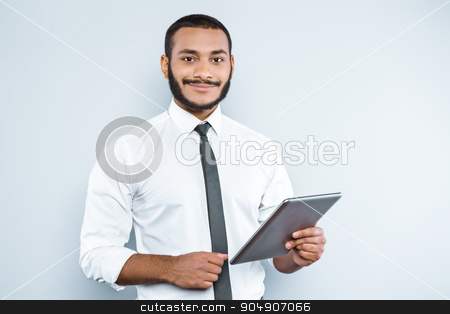Freestyle photo with young mulatto stock photo, Young mixed race businessman with beard standing on grey background. Young man smiling and holding tablet computer by Dmytro Sidelnikov