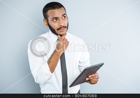 Freestyle photo with young mulatto stock photo, Young mixed race businessman with beard standing on grey background. Young man holding tablet computer by Dmytro Sidelnikov