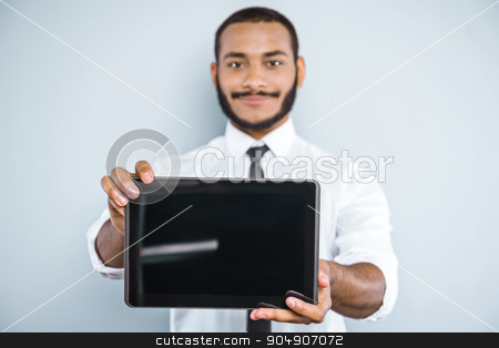 Freestyle photo with young mulatto stock photo, Young mixed race businessman with beard standing on grey background. Young man smiling and showing tablet computer by Dmytro Sidelnikov