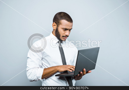 Freestyle photo with young mulatto stock photo, Young mixed race businessman with beard standing on grey background. Young man using laptop by Dmytro Sidelnikov