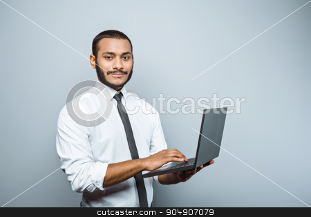 Freestyle photo with young mulatto stock photo, Young mixed race businessman with beard standing on grey background. Young man using laptop and looking at camera by Dmytro Sidelnikov