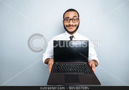 Freestyle photo with young mulatto stock photo, Young mixed race businessman with beard standing on grey background. Young man showing laptop by Dmytro Sidelnikov