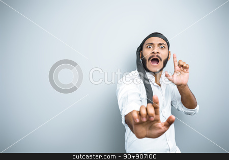 Freestyle photo with young mulatto stock photo, Fun picture of young mixed race man with beard standing on grey background. Young man with tie on head by Dmytro Sidelnikov