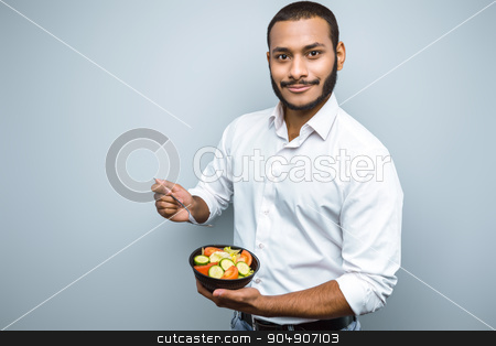 Freestyle photo with young mulatto stock photo, Young mixed race man with beard standing on grey background. Young man holding plate with salad by Dmytro Sidelnikov