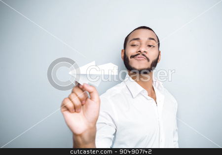 Freestyle photo with young mulatto stock photo, Young mixed race man with beard standing on grey background. Young man starting up paper plane by Dmytro Sidelnikov