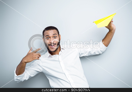 Freestyle photo with young mulatto stock photo, Young mixed race man with beard standing on grey background. Young man starting up yellow paper plane by Dmytro Sidelnikov