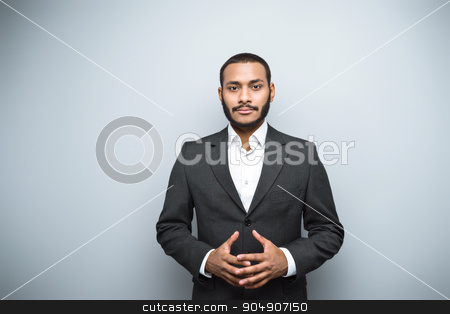Freestyle photo with young mulatto stock photo, Young mixed race businessman with beard and suit standing on grey background. Young man looking at camera by Dmytro Sidelnikov