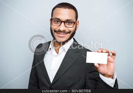 Freestyle photo with young mulatto stock photo, Young mixed race businessman with beard and suit standing on grey background. Young man smiling and holding visit card by Dmytro Sidelnikov