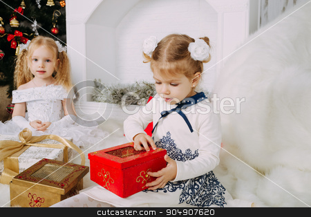 Cute beautiful girl opens Christmas gift stock photo, Two blond little girls with Christmas gifts by sunapple