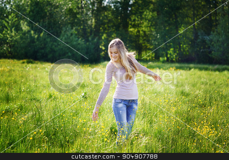 happy beautiful woman walking on a spring meadow stock photo, happy beautiful woman walking on a spring meadow. by timonko