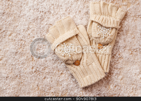white knitted mittens in the snow stock photo, white knitted mittens in the snow. by timonko