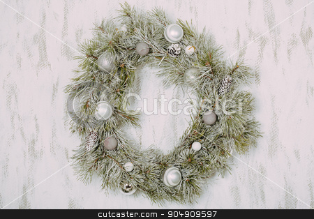 Snowy wreath at the wall stock photo, Christmas wreath with toys and cones by sunapple