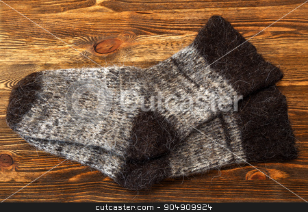 Knitted wool socks stock photo, Knitted wool socks on a brown wooden background by ires007