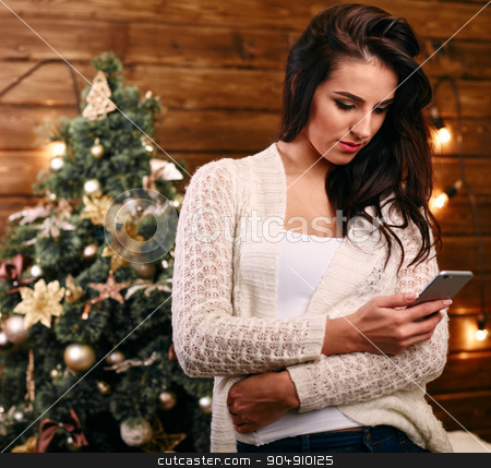 Attractive festive young woman  in front of the Xmas tree checking for Christmas messages on her mobile phone stock photo, Attractive festive young woman  in front of the Xmas tree checking for Christmas messages  by mykhalets